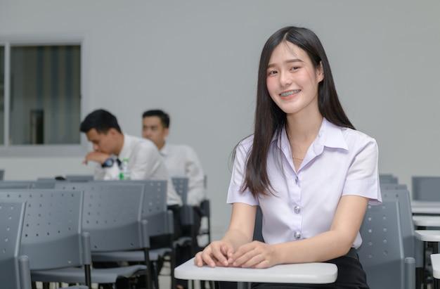Retrato de linda estudiante asiática con tirantes en los dientes