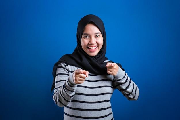 Retrato de linda hermosa dama musulmana asiática sonriendo a la cámara y apuntando hacia adelante como si eligiera su concepto contra el fondo azul.