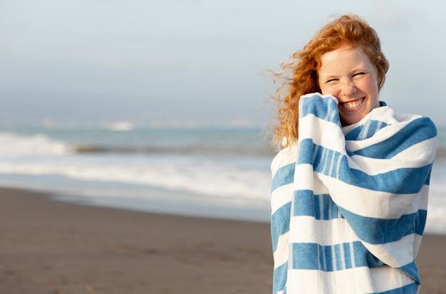 Retrato de linda joven disfrutando de tiempo en la playa