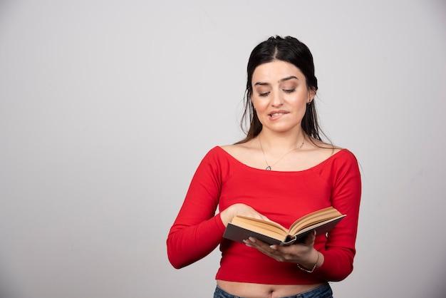 Retrato de linda joven estudiante morena mirando un libro abierto.