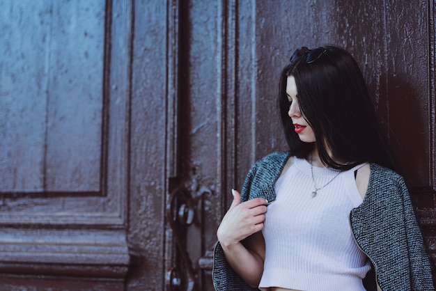 Retrato de una linda joven morena con labios rojos y una camiseta blanca