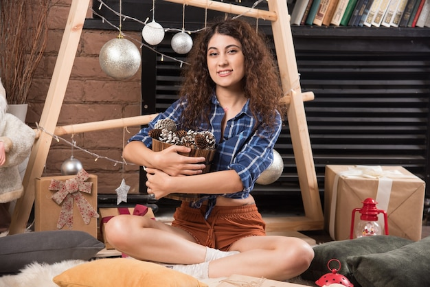 Retrato de una linda joven sosteniendo una canasta de madera de piñas