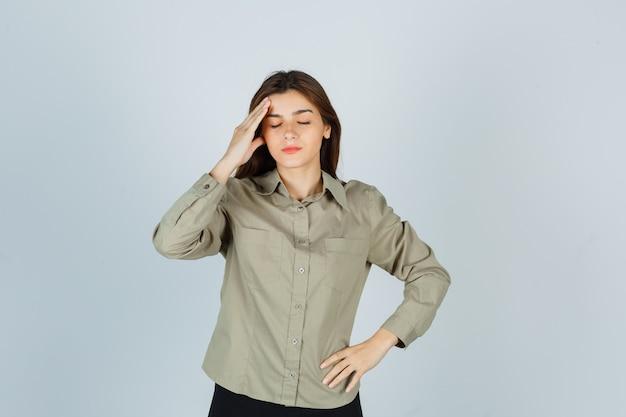 Retrato de linda mujer joven con dolor de cabeza, frotándose la frente en camisa, falda y mirando fatigada vista frontal