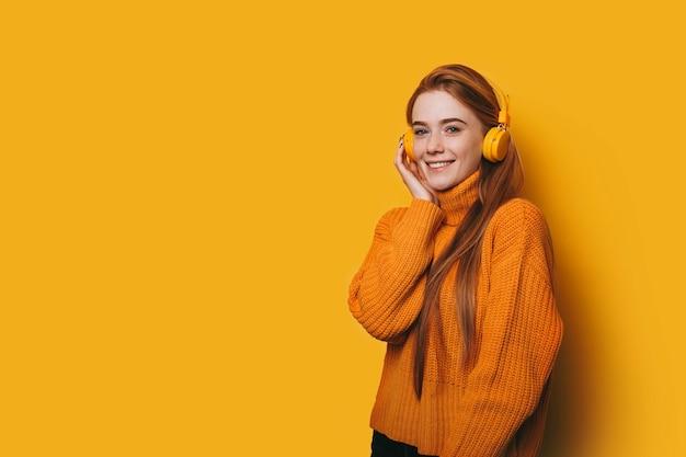 Retrato de linda mujer joven con pelo rojo y pecas mirando a la cámara sonriendo mientras escucha música en auriculares amarillos contra la pared amarilla.