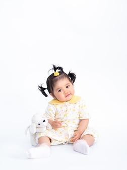 Retrato de linda niña asiática con muñeca cachorro