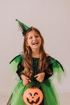 Retrato de una linda niña feliz en un disfraz de halloween lanzando confeti sobre un fondo gris