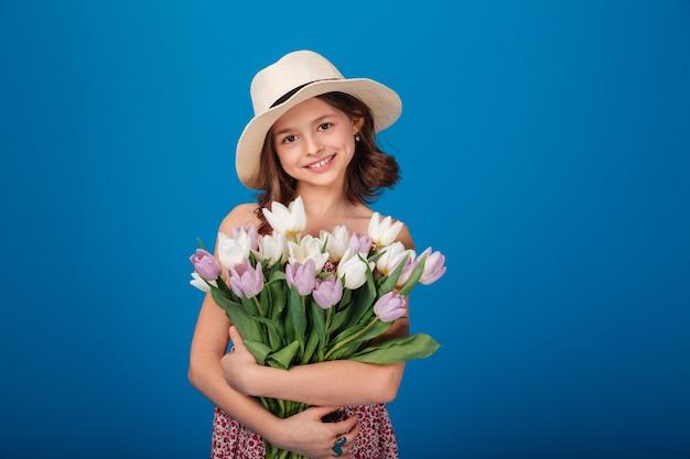 Retrato de linda niña feliz con ramo de flores sobre fondo azul.