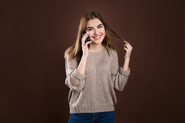 Retrato de una linda niña feliz en suéter hablando por teléfono móvil y riendo aislado sobre suéter