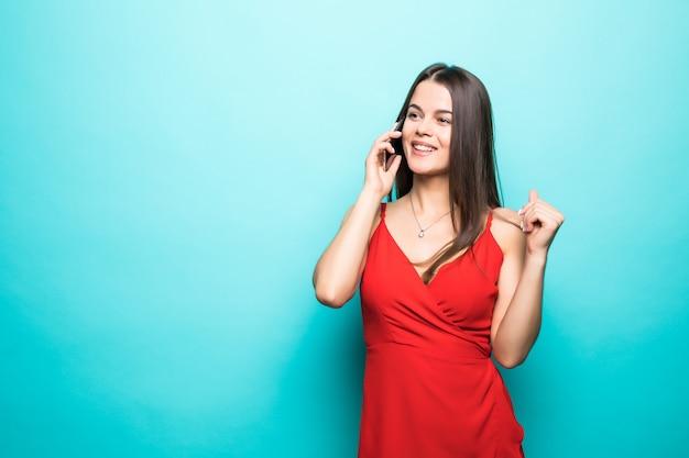 Retrato de una linda niña feliz en vestido hablando por teléfono móvil y riendo aislado sobre pared azul