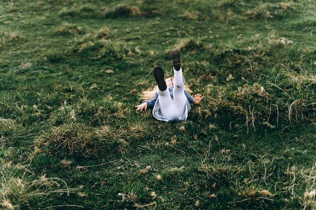 Retrato de una linda niña hermosa y feliz corriendo por el campo soleado