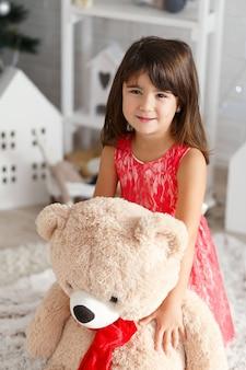 Retrato de una linda niña morena abrazando a un osito de peluche grande y suave en el interior con adornos navideños