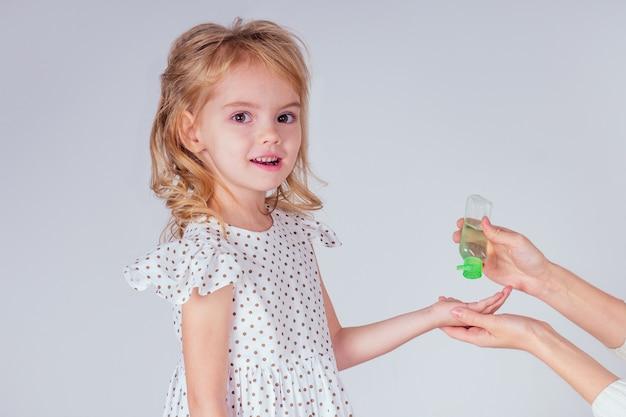 Retrato de una linda niña rubia aplicando gel antiséptico antibacteriano en las manos contra virus de bacterias en estudio sobre fondo blanco. protección contra la epidemia del bebé, mano de la madre de primer plano.