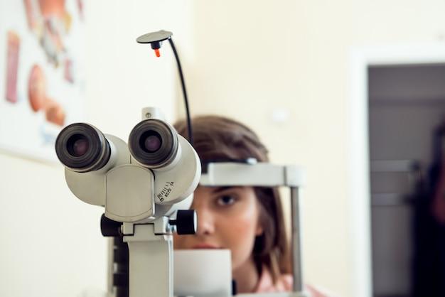 Retrato de linda paciente mujer caucásica sentado en la oficina del optometrista, esperando el inicio del procedimiento para comprobar su visión con microbioscopio, sentado sobre la pared amarilla. concepto de oftalmología