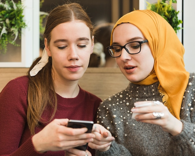 Retrato de lindas chicas jóvenes revisando un teléfono
