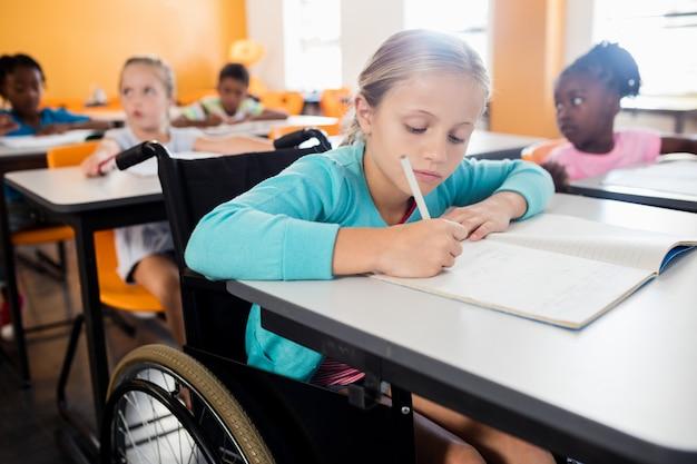 Retrato de un lindo alumno en silla de ruedas trabajando en el escritorio