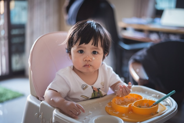 Retrato de lindo bebé comiendo sucio en la mesa