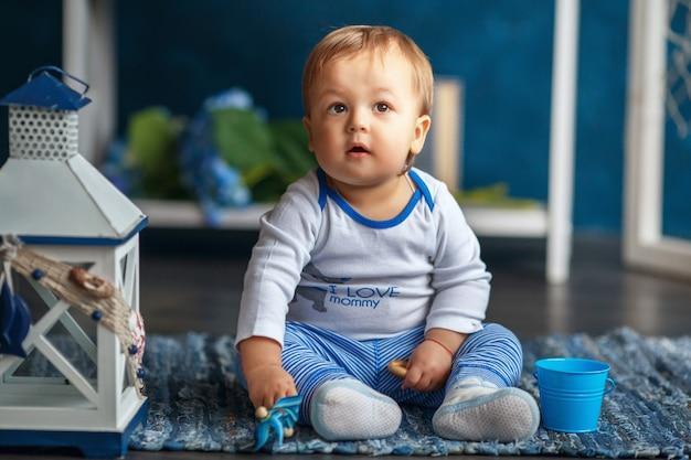 Retrato de un lindo bebé niño en el interior con estilo mar