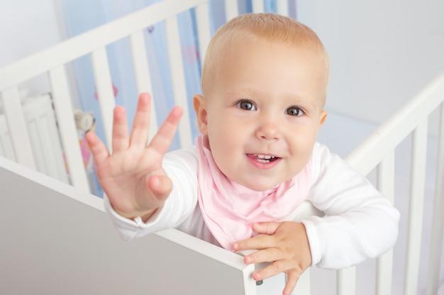 Retrato de un lindo bebé saludando y sonriendo desde la cuna