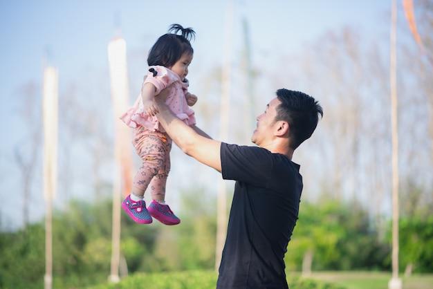 Retrato de lindo bebé y su papá viajan en el jardín de flores