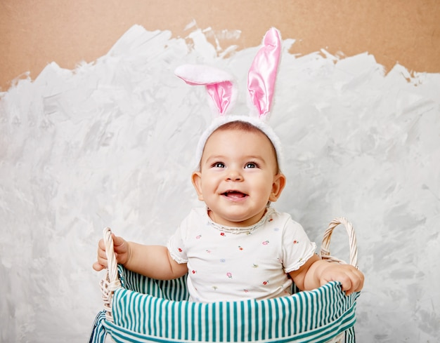 Retrato de un lindo bebé vestido con orejas de conejo de pascua en una cesta tiene huevo