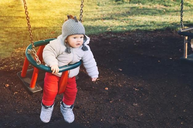 Retrato de lindo bebé vestido con ropa de abrigo en columpio en el patio de recreo en un día soleado al aire libre.
