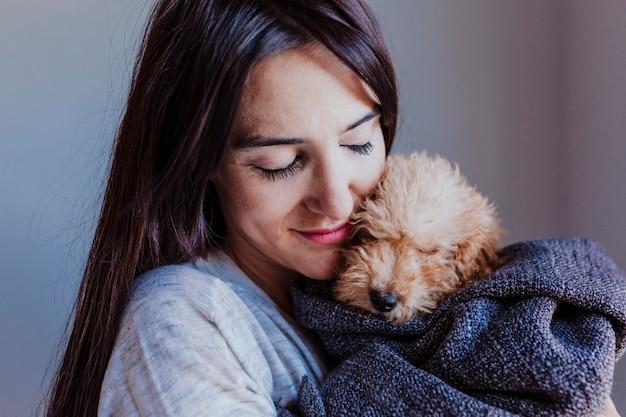 Retrato de un lindo caniche de juguete marrón con su joven dueña en casa, durante el día, en el interior.