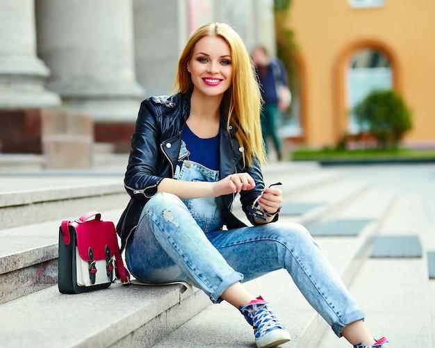 Retrato de lindo gracioso moderno sexy urbano joven elegante sonriente mujer niña modelo en tela moderna brillante al aire libre sentado en la ciudad en jeans con bolsa rosa