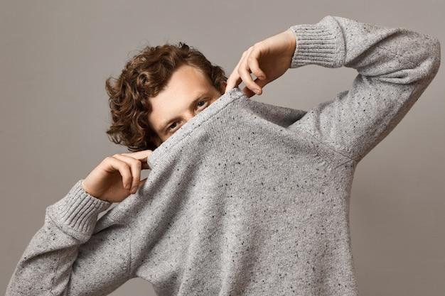 Retrato de un lindo joven caucásico de aspecto moderno con peinado rizado voluminoso ondulado jugando, tirando un suéter gris sobre su rostro, dejando los ojos abiertos, con expresión facial segura