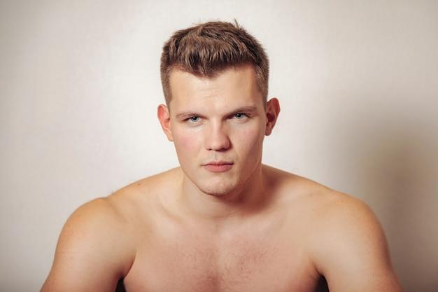 Retrato de lindo joven de complexión atlética sobre fondo claro aislado. hombre guapo y musculoso