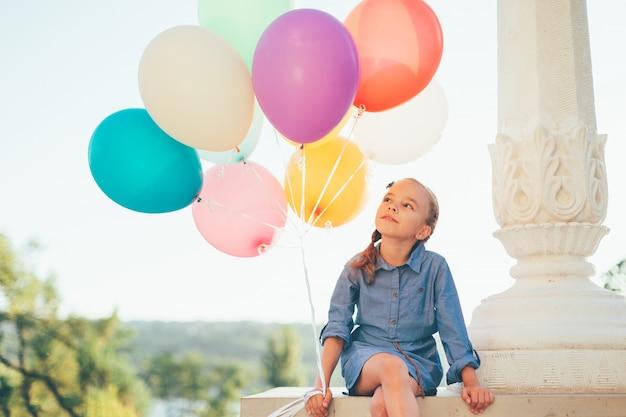 Retrato lindo de la muchacha que sostiene los globos coloridos en el parque de la ciudad