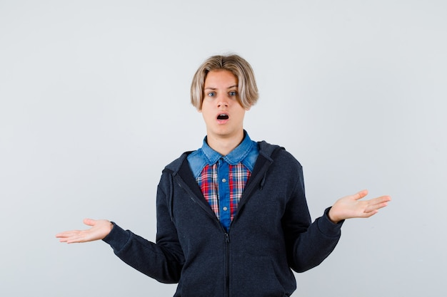 Retrato de lindo muchacho adolescente mostrando gesto de impotencia en camisa, sudadera con capucha y mirando desconcertado vista frontal