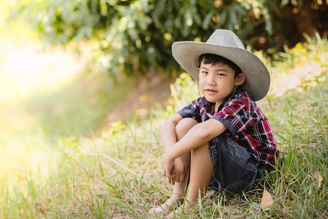 Retrato lindo niño asiático sentado en la hierba
