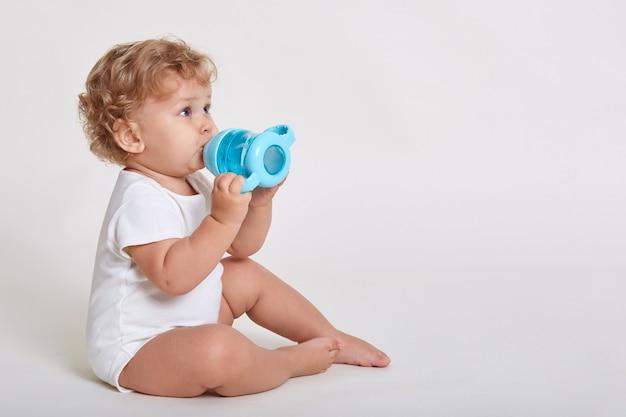 Retrato de lindo niño bebiendo agua de botella mientras está sentado contra la pared blanca, vistiendo traje de cuerpo