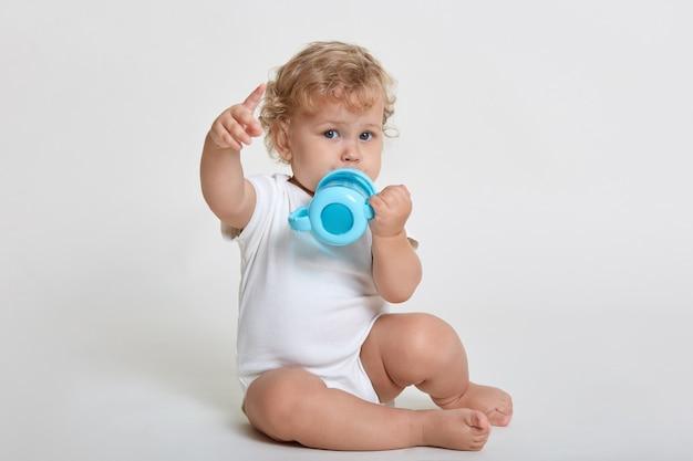 Retrato de lindo niño bebiendo agua de la taza de la botella azul, indicando lejos con su dedo índice