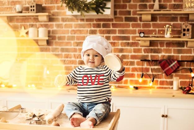Un retrato de un lindo niño cocinado y jugado con harina y masa en la cocina.