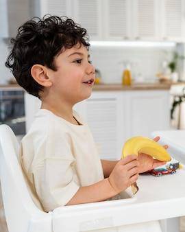 Retrato de lindo niño desayunando en la silla del niño