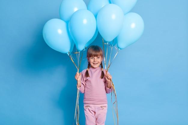 Retrato de lindo niño en edad preescolar posando contra la pared azul con globos