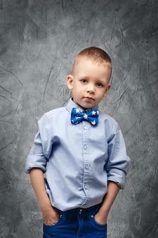 Retrato de un lindo niño en jeans, camisa azul y pajarita