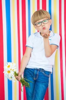 Retrato lindo del niño lindo en colorido. adorable niño parado cerca de la pared. niño con un ramo de flores.