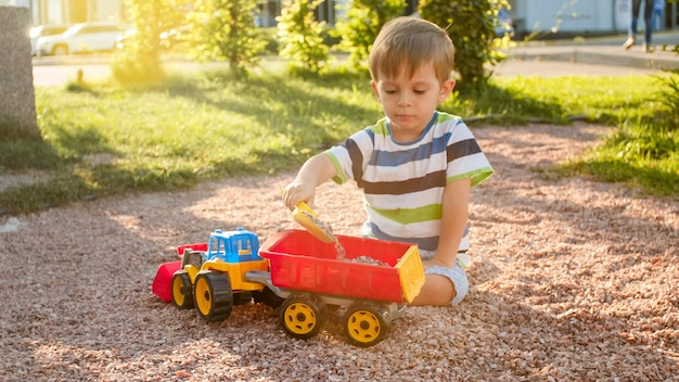 Retrato de lindo niño pequeño de 3 años sentado en el patio de recreo en el parque y jugando con coloridos camiones de juguete de plástico
