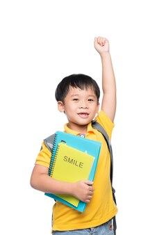 Retrato de lindo niño sonriente con mochila y libros coloridos con la mano levantada