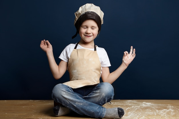 Retrato de lindo niño varón europeo en uniforme de chef sentado con las piernas cruzadas sobre un piso de madera con harina derramada, cerrando los ojos como si meditara. infancia, cocina, repostería, panadería, afición y relajación