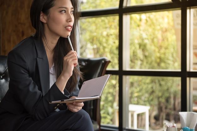 Retrato de la localización atractiva de la empresaria en el sofá que sostiene el cuaderno y el pensamiento pensativo sobre trabajo.
