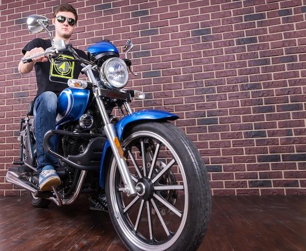 Retrato de longitud completa de ángulo bajo de joven sentado en la clásica motocicleta azul delante de la pared de ladrillo