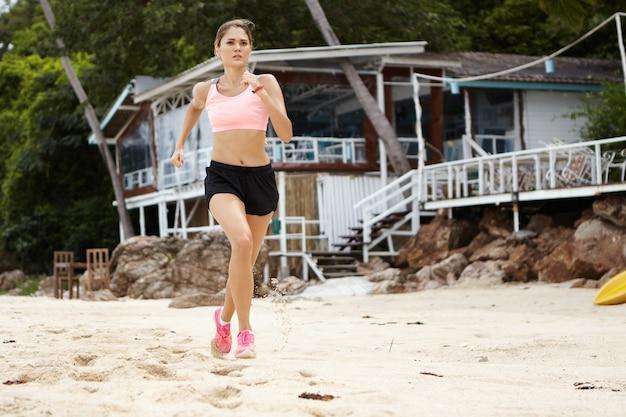 Retrato de longitud completa de la corredora rubia en ropa deportiva y zapatillas rosa trotar en la hermosa playa de arena habiendo determinado una expresión seria mientras entrenaba para el maratón.