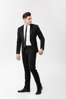 Retrato de longitud completa hombre de negocios posando con estilo sobre fondo blanco.