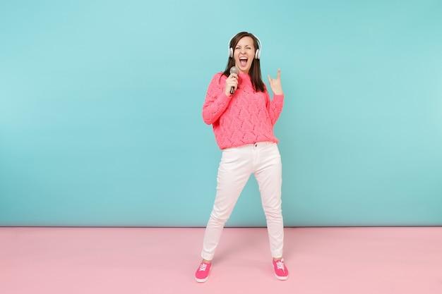 Retrato de longitud completa mujer divertida en suéter de punto, pantalón blanco, auriculares cantan canción en micrófono