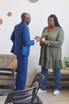 Retrato de longitud completa vertical de dos personas afroamericanas hablando durante la pausa para el café en la reunión del grupo de apoyo