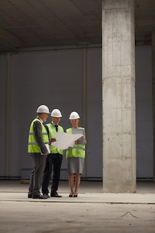 Retrato de longitud completa vertical de gente de negocios vistiendo cascos y sosteniendo planes mientras está de pie en el sitio de construcción en el interior,