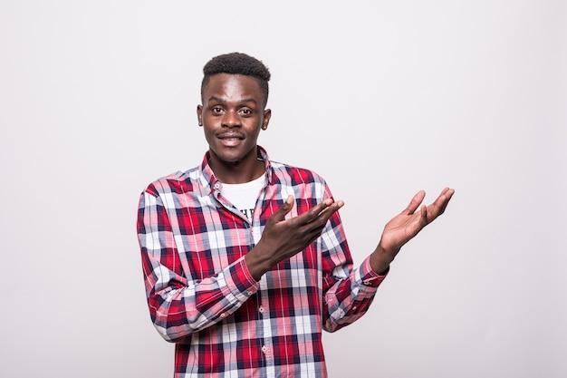 Retrato con lugar vacío hombre afroamericano con sonrisa radiante apuntando con dos dedos índices para copiar el espacio, mirando, aislado